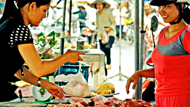 A local pork vendor at the wet market sells her meat to two local women, Hung Yen province, Vietnam (photo credit: ILRI/Nguyen Ngoc Huyen).